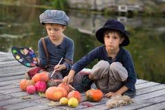 愉快的孩子油漆小万圣夜南瓜 免版税图库摄影
