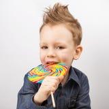愉快的孩子用在白色背景隔绝的一个大糖果 免版税库存照片