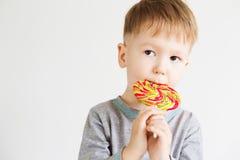 愉快的孩子用在白色背景隔绝的一个大糖果 库存图片
