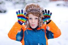 愉快的孩子男孩获得与雪的乐趣在冬天 免版税图库摄影