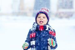 愉快的孩子男孩获得与雪的乐趣在冬天 免版税库存照片