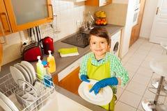 愉快的孩子男孩洗涤的盘在国内厨房里 免版税图库摄影