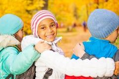 愉快的孩子站立接近与在肩膀的胳膊 库存照片