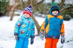 愉快的孩子获得与雪的乐趣在冬天 免版税库存照片