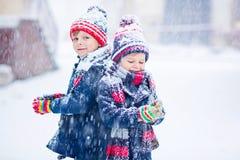 愉快的孩子获得与雪的乐趣在冬天 免版税图库摄影