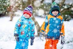 愉快的孩子获得与雪的乐趣在冬天 免版税库存图片