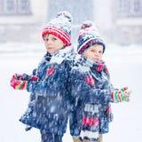 愉快的孩子获得与雪的乐趣在冬天 库存照片