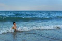 愉快的孩子获得乐趣在海边 免版税图库摄影