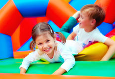 愉快的孩子获得在操场的乐趣在幼儿园 免版税库存照片