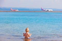 愉快的孩子观看的飞机着陆在海滩机场 免版税图库摄影