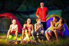 愉快的孩子讲有趣的故事在营火附近 免版税库存图片