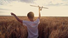 愉快的孩子跑与在日落背景的一架玩具飞机在麦田 免版税库存照片