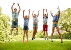 愉快的孩子跳跃和获得乐趣在夏天公园 免版税库存图片
