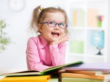 愉快的孩子阅读书和作梦 免版税库存图片