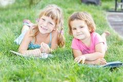 年轻愉快的孩子,儿童在自然backgrou的阅读书 免版税库存照片