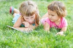 年轻愉快的孩子,儿童在自然backgrou的阅读书 免版税库存图片