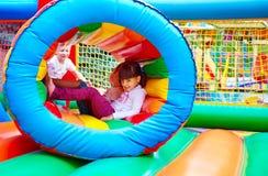 愉快的孩子,获得在可膨胀的吸引力操场的乐趣 库存照片