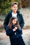 愉快的孩子 姐妹和兄弟步行在公园 免版税库存图片