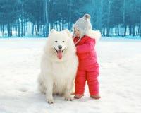 愉快的孩子画象有白色萨莫耶特人狗的在冬天 免版税图库摄影