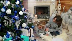 愉快的家庭、使用在圣诞树附近的母亲和女儿,在舒适大气在房子里,趣味游戏与 影视素材