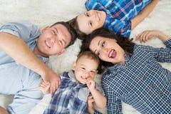 愉快的家庭、母亲、的父亲和获得两个的儿子乐趣说谎在地板上的,上部看法 免版税图库摄影
