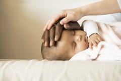 愉快的家庭、母亲和父亲关心睡觉的婴孩 免版税库存照片