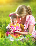 愉快的家庭。妈妈和婴孩在一个草甸在夏天在公园 库存图片