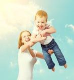 愉快的家庭。母亲投掷天空的婴孩 免版税库存照片