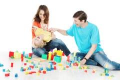 愉快的家庭。演奏与孩子的父母玩具块 免版税库存照片