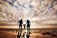 愉快的家庭一起手拉手在海滩 库存照片