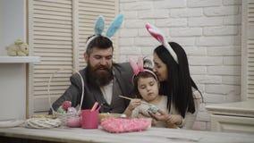 愉快的家庭为复活节做准备 逗人喜爱的小孩女孩佩带的兔宝宝耳朵 母亲、父亲和他们的女孩绘画 股票录像