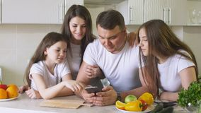愉快的家庭为购物使用一个智能手机在互联网上 免版税库存照片