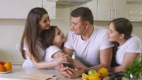 愉快的家庭为购物使用一个智能手机在互联网上 库存图片