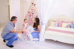 愉快的家庭交换礼物在宽敞卧室在backgro点燃 免版税库存图片