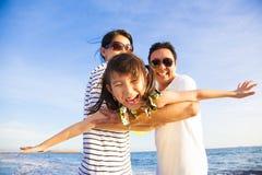 愉快的家庭享受在海滩的暑假 免版税库存照片
