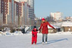 愉快的家庭冰鞋在冬天 免版税库存照片