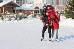 愉快的家庭冰鞋在冬天 免版税库存图片