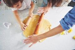 愉快的家庭准备假日食物概念 烹调圣诞节曲奇饼的家庭 母亲和女儿准备的手 库存图片