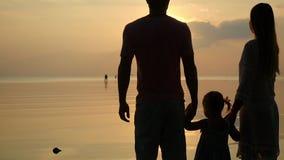 愉快的家庭剪影在日落的 父亲、母亲和女儿 爸爸和妈咪保留女儿的手 慢的行动 股票录像