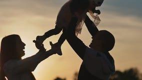 愉快的家庭剪影在晚上日落光芒的  女儿是在教皇的手里 他快乐培养 股票录像