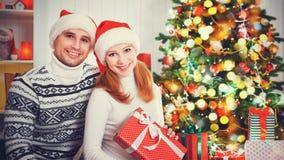 愉快的家庭加上在圣诞节的一件礼物在家 免版税库存图片