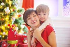 愉快的家庭和圣诞快乐 母亲和小儿子在圣诞节早晨 免版税库存照片