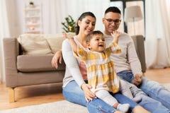 愉快的家庭和在家使用小的女儿 免版税库存图片