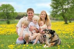 愉快的家庭和爱犬在花草甸 免版税库存图片