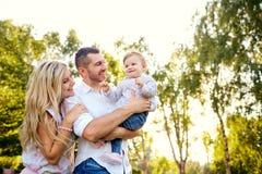 愉快的家庭在一个公园在夏天秋天 免版税图库摄影