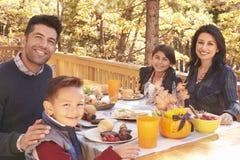 愉快的家庭在一个甲板的一张桌上对照相机的森林神色的 免版税库存图片