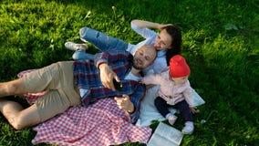 愉快的家庭在与婴孩的恳求的和做的selfie放置在日落在公园 父母拍照片 库存图片