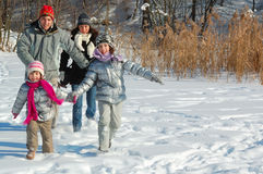 愉快的家庭在冬天,获得与雪的乐趣户外 免版税库存图片