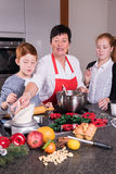 愉快的家庭在准备圣诞节面包店的厨房里 免版税库存照片
