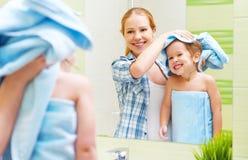 愉快的家庭在卫生间里 一个孩子的母亲有毛巾干毛发的 免版税库存图片